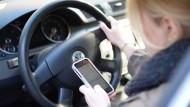 Abgelenkt beim Autofahren: Schon der kurze Blick aufs Handy kann tödlich sein.