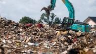 Ein Bagger fährt am 27. Juli 2021 in Swisttal auf einen riesigen Müllberg auf einer Wiese vor dem Ort.