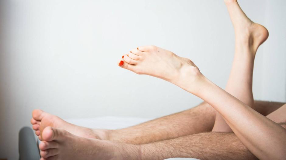 Ein junges Paar liegt im Bett (Symbolbild).