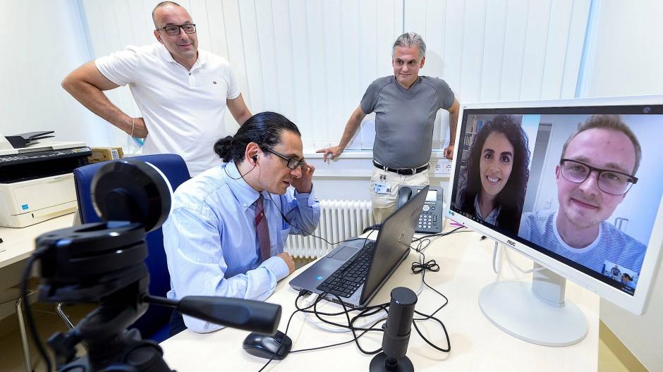 Schauspieler Michele Marotta (sitzend am PC) in einer gestellten Videosprechstunde mit den Studenten Oras Obuda und Moritz Möhler (auf dem Bildschirm)