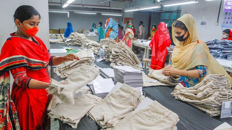 Mitarbeiterinnen einer Bekleidungsfabrik in Bangladesch sortieren Shorts. Wie sollen deutsche Unternehmen dortige mögliche Missstände kontrollieren?