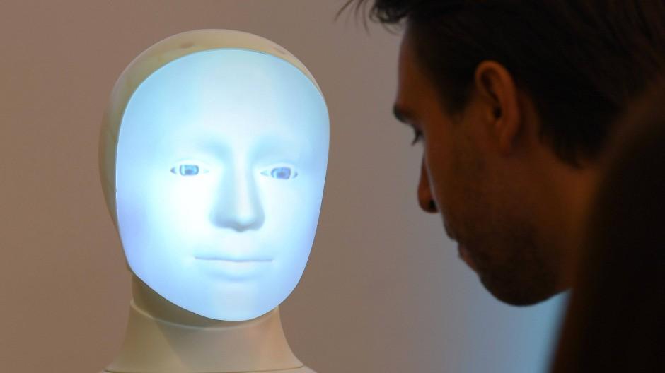 Ein Forscher aus Darmstadt kommuniziert mit einem Roboter.