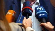 Viele Mikrophone, viele Sender, ein System: Reporter der Öffentlich-Rechtlichen bei einem Pressetermin.