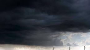 Über drei Windrädern in Sachsen ziehen dunkle Gewitterwolken auf