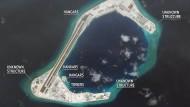 """Die Satellitenbilder der Asia Maritime Transparency Initiative (AMTI) zeigen das aufgeschüttete Subi Korallenriff. """"Hangars"""" heißt """"Flugzeughallen"""", """"towers"""" heißt """"Türme"""" und der Begriff """"unknown structure"""" steht für """"unbekannte Strukturen""""."""
