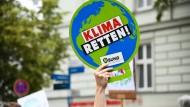 """Ein Teilnehmer hält während einer Demonstration des Bündnisses """"Potsdam for Future"""" ein Schild hoch."""