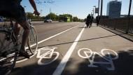 Linksherum: Fahrradweg (links) und Fahrradsignet auf dem Bürgersteig für Falschfahrer (rechts) auf der Friedensbrücke in Frankfurt