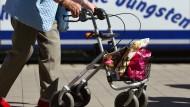 Eine Seniorin läuft in Kleinmachnow (Brandenburg) mit ihrem Rollator an einem Bus vorbei.