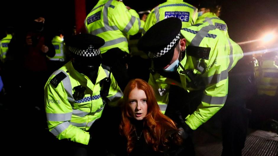 Polizisten nehmen bei einer Mahnwache für die getötete Sarah E. in London eine Frau fest.