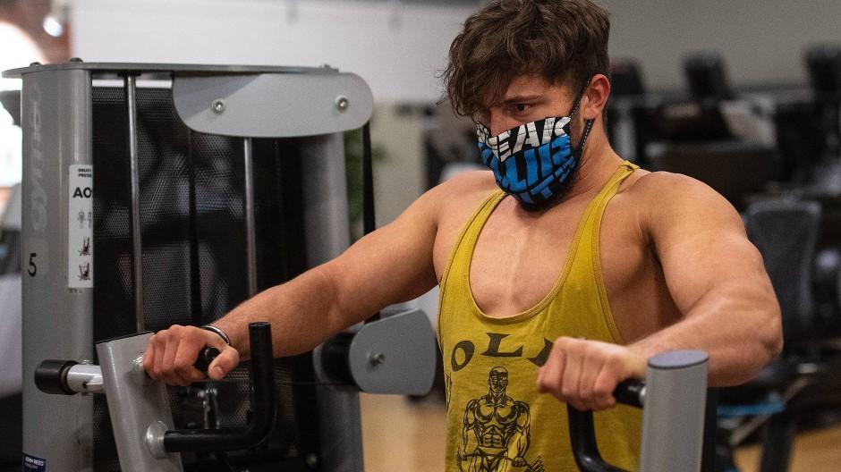 Ein Mann trainiert während der Corona-Krise im Fitnessstudio mit Atemschutzmaske