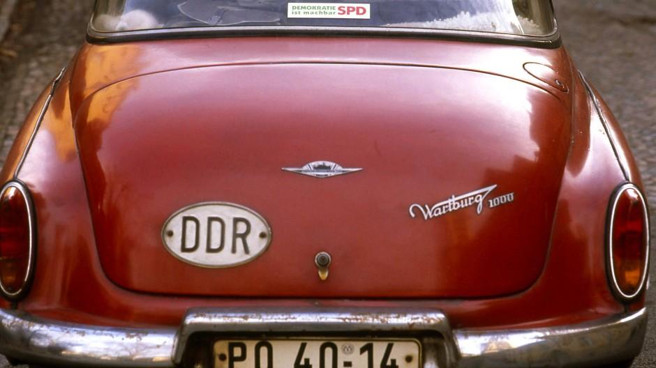 Von diesem Fahrzeugheck sehen vier Jahrzehnte zu uns hinauf: Ein Wartburg aus der DDR mit einem Wahlkampfaufkleber der SPD aus dem Jahr 1990.
