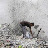 Ein Müllsammler durchsucht in der Manila Bay auf den Philippinen den von starken Wellen an Land gespülten Müll.
