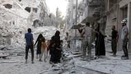 Eine Familie irrt durch die Ruinen von Aleppo.