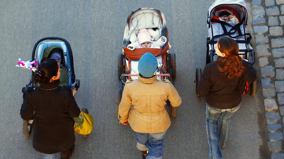 Drei junge Mütter schieben ihre Babys im Kinderwagen bei einem gemeinsamen Spaziergang.