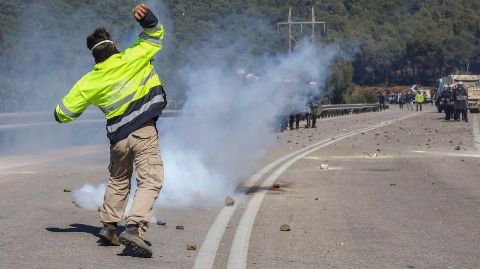 Ein Demonstrant wirft am Mittwoch auf der griechischen Insel Lesbos einen Stein in Richtung von Polizisten.