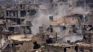 Im Osten Aleppos steigt Rauch aus Ruinen, nachdem regierungstreue Truppen vorgerückt sind.