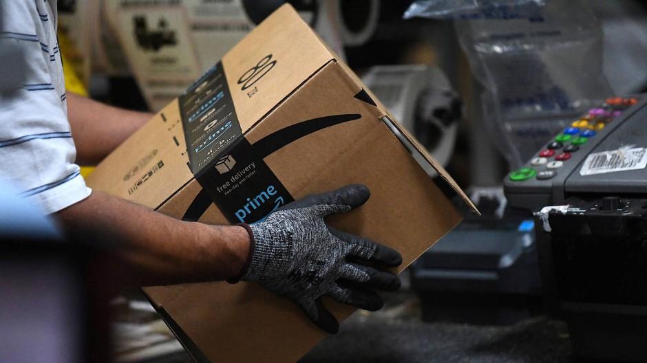 Dieses Packet, welches ein Amazon-Mitarbeiter im Verteilzentrum in Maryland trägt, ist noch verpackt. Retouren in Amerika müssen nun nicht mehr verpackt werden.