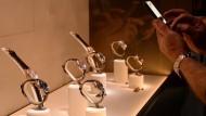 """Ein Besucher der internationalen Uhrenmesse """"Baselworld"""" hält die Objekte der Begierde mit seiner Handykamera fest."""