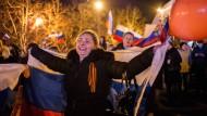 Nach dem großen Zuspruch für einen Anschluss an Russland feiern Bürger auf der Krim mit russischen Flaggen das Wahlergebnis