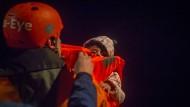 Ein Besatzungsmitglied des deutschen Rettungsschiffes Alan Kurdi nimmt ein Kleindkind an Bord.