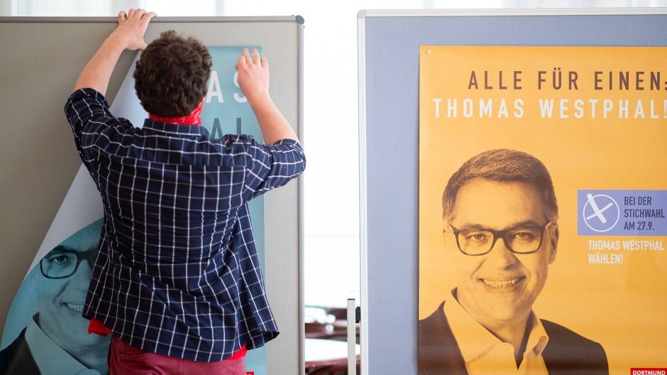 Ein Wahlhelfer hängt zwei Plakate von Thomas Westphal auf, dem Oberbürgermeisterkandidaten der SPD für Dortmund.