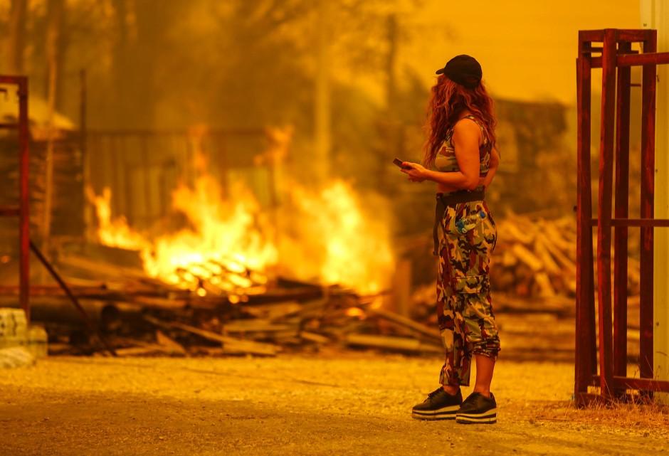 Eine Frau nahe dem Touristenziel Manavgat beobachtet die wütenden Flammen.