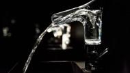Wasser sprudelt aus einem gläsernen Wasserhahn.