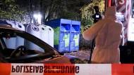 Ein Mitarbeiter der Spurensicherung fotografiert vor Glas- und Kleidercontainern am Rand eines Waldes.