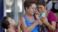 Zwei Kubanerinnen halten ein Smartphone in der Hand. Seit Anfang Dezember haben die Menschen dort dauerhaft Zugang zu mobilem Internet.