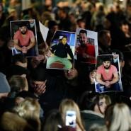 Demonstranten halten am Donnerstagabend in Hanau Fotos der Getöteten in die Luft.