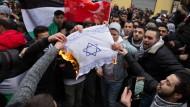 Teilnehmer einer Demonstration verbrennen am Sonntag eine selbstgemalte Fahne mit einem Davidstern in Berlin im Stadtteil Neukölln