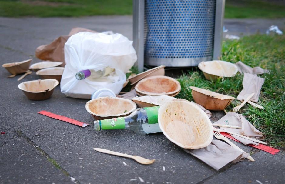 Müllreste und Einweggeschirr neben einem vollen Mülleimer