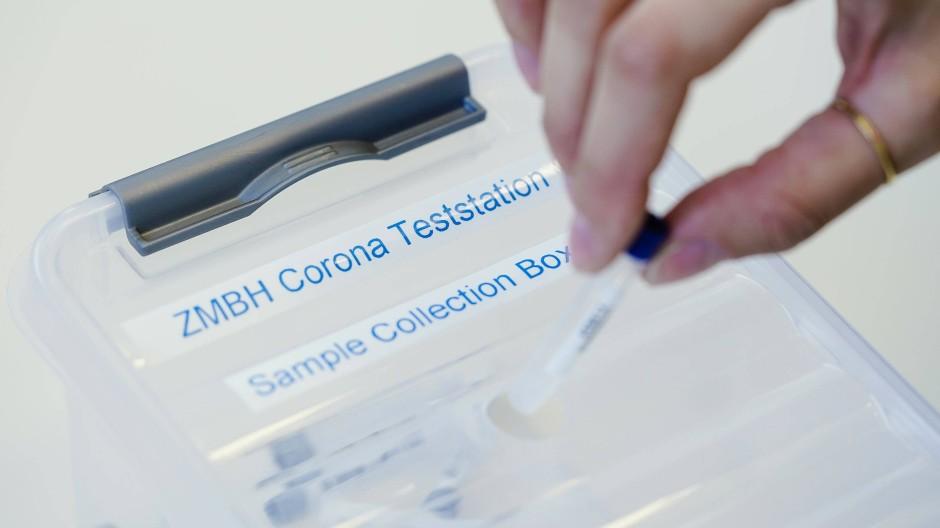 Eine Mitarbeiterin wirft in einem Labor ein Teströhrchen in eine Sammelbox.