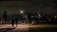 In Frankfurt am Main laufen Jogger an einem Polizeiauto vorbei.