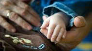 In einem deutschen Hospiz für todkranke Kinder hält eine Krankenschwester die Hand eines Kindes. In Deutschland gibt es keine Sterbehilfe für Kinder.