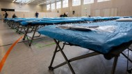 Für Verdachtsfälle des Coronavirus: Aufgeklappte Feldbetten in einer Turnhalle auf dem Frankfurter Flughafen.
