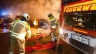 Feuerwehrleute versuchen ein brennendes Auto zu löschen.