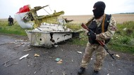 Ein pro-russischer Separatist steht vor einem Wrackteil des abgeschossenen Flugzeugs in der Ukraine im Juli 2014.
