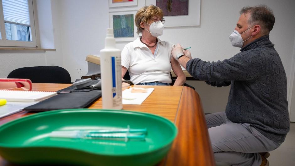 Ein Arzt impft eine Frau in einer Hausarztpraxis mit dem Impfstoff von Pfizer/Biontech.
