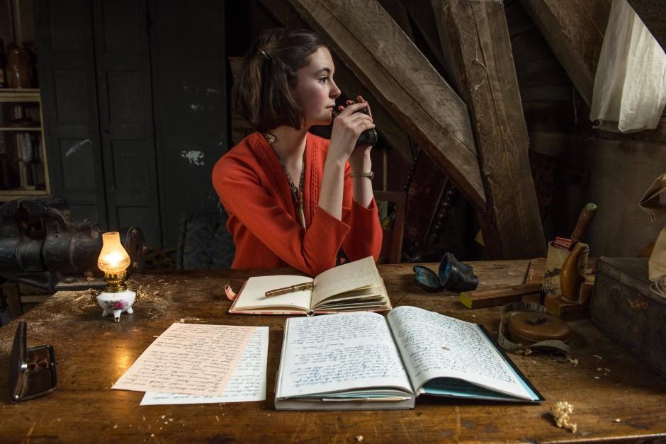 Lea van Acken als Anne Frank schreibt in einer Szene des Films «Das Tagebuch der Anne Frank» in einer Kammer unterm Dach an ihrem Tagebuch.