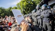 Vor einer Reihe von Polizisten hält ein Teilnehmer der Demonstration in Berlin das Grundgesetz in die Höhe.
