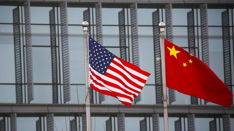 Die amerikanische und chinesische Flagge vor einem Firmengebäude in Peking