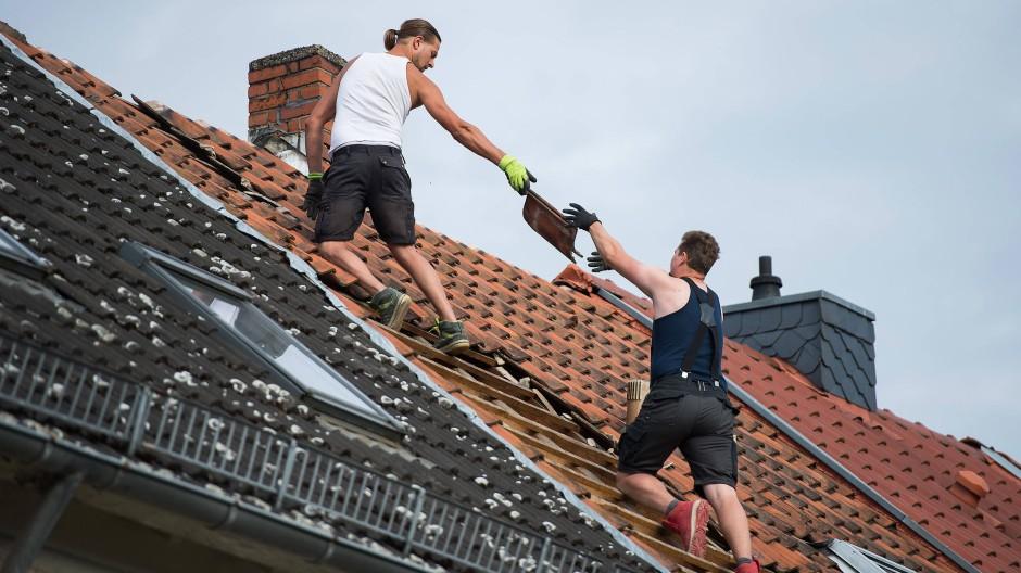 Dachdecker decken das Dach eines Wohnhauses ab.
