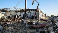 Migranten suchen nach dem Angriff auf das Lager bei Tripolis in den Trümmern nach ihren Habseligkeiten.
