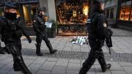 Am Tatort: Sicherheitskräfte patrouillieren in der Straßburger Innenstadt, wo Passanten Blumengebinde für die Opfer des Anschlags niedergelegt haben.