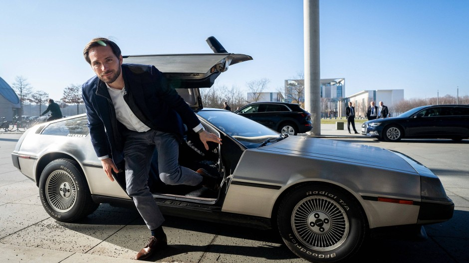 """Christoph Weigler steigt vor einer Bundestags-Anhörung aus dem """"Zurück in die Zukunft"""" - DeLorean."""
