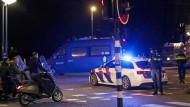 Polizisten sprechen am Dienstagabend in Amsterdam mit Jugendlichen auf Motorrollern.