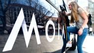 Ein Fahrgast steigt im Stadtzentrum von Hannover in einen Volkswagen T6 des Mobilitätsunternehmens Moia ein.