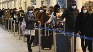 Reisende mit Mund-Nasen-Bedeckungen warten im Bahnhof St. Pancras in London in einer Schlange, um den letzten Zug nach Paris zu nehmen