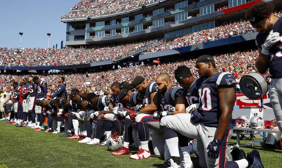 Juli 2017, Foxborough: Einige Spieler des Football-Teams New England Patriots knien während der amerikanischen Nationalhymne auf dem Rasen.